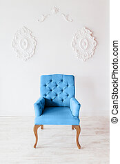 Classic blue chair on white wall background with swirl decorations. Studio interior.