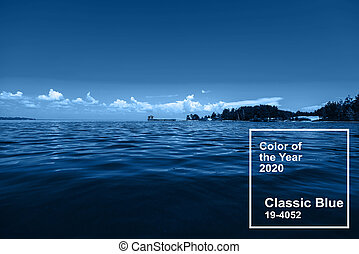 Classic Blue pantone color of the Year 2020. blue sky with white clouds over water on a summer day