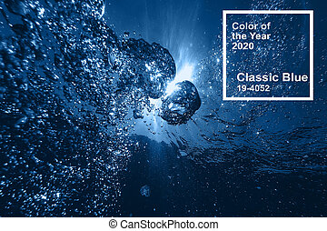 Classic blue pantone main color trend of the Year 2020. air bubbles at water surface in sea in clear blue water