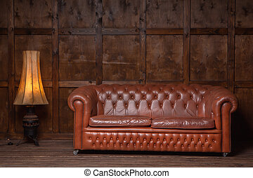 Classic brown loft style interior with wood paneling, chesterfield sofa. Old sofa on the background of vintage wall. High quality photo