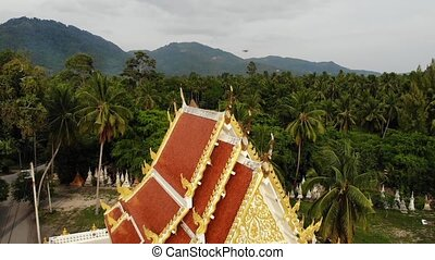 Classic Buddhist temple between forest. From above drone view Buddhist monastery between green trees near hill in Thailand. Koh Samui. concept of tourism, meditation and oriental life. Asian village