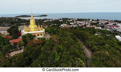 Classic Buddhist temple between forest. From above drone view Buddhist monastery between green trees near hill in Thailand. Koh Samui. concept of tourism, meditation and oriental life. Asian village.