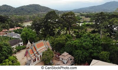 Classic Buddhist temple between forest. From above drone view classic Buddhist monastery between green trees near hill in Thailand. Koh Samui. concept of tourism, meditation and oriental life.