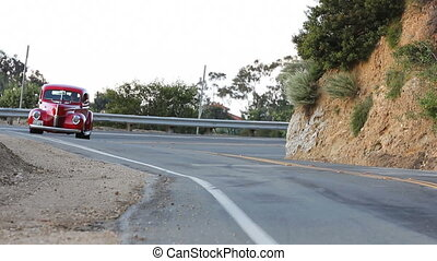A come & go edit of a red restored 1940 classic car coming around the corner of a mountainous road.