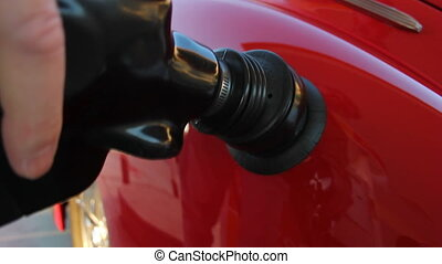 This is a close up shot of a classic car getting filled up with gasoline.