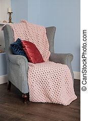 classic chair with pillows on in vintage style bedroom interior. Pink Plaid Blanket Woolen Knitted on grey Chair, Scandinavian Style. Cozy and comfortable room