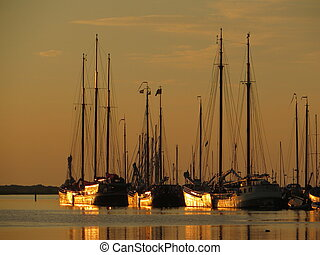 Classic Charter sailboats in the evening sun in Makkum (Holland)