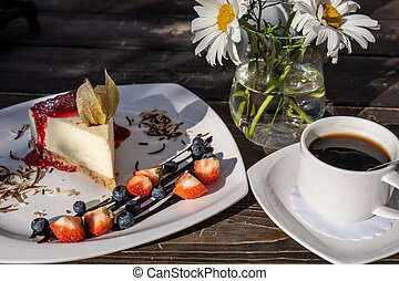classic cheesecake with raspberry jam on a plate decorated with fresh strawberries and cup of coffee
