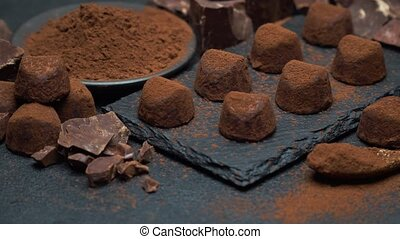 classic chocolate truffles and pieces of chocolate on dark...