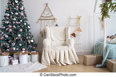 Classic covered armchair beside decorated Christmas tree with a ladder and dream catcher hanged on the wall