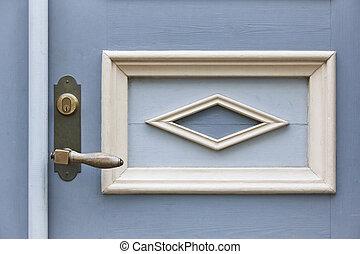 Classic doorknob on a vintage blue wooden door. Decoration