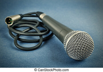 Classic dynamic microphone on a blue  background. Toned