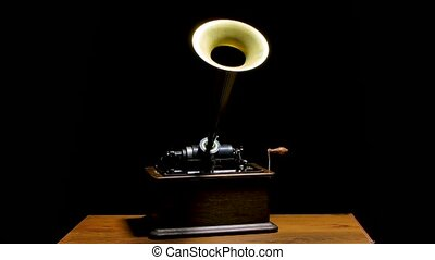 Classic Edison Phonograph on a wooden table in a dark studio. Retro vintage machine to reproduce sound making listening to music. Slow motion