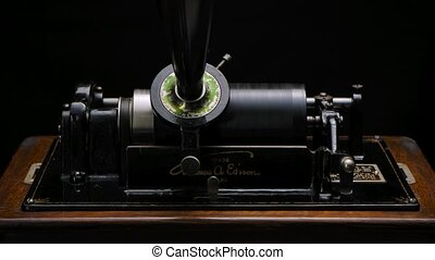 Classic Edison Phonograph plays music through the horn on a black studio background. Retro vintage machine to reproduce sound making listening to music. Close up. Slow motion