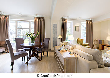 Elegant living room with a large sofa and a round, classic coffee table in a spacious house interior