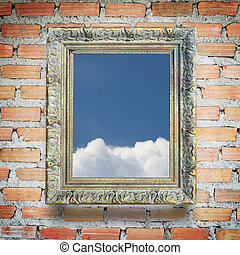 Classic frame with blue sky and white cloud, on brick wall background.