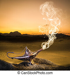 classic gold-colored aladdin lamp laid on the sand of a dune...
