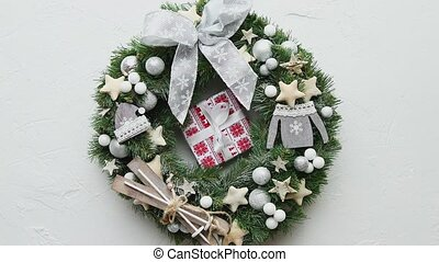 Classic, handmade Christmas wreath made with wooden decorations, balls, stars and bow. With small boxed gift in the middle. Placed on stone background. Top view, flat lay.
