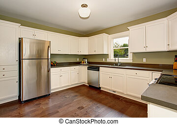 Classic kitchen with green interior paint, and white cabinets.
