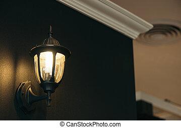 Classic lamp on black wall.