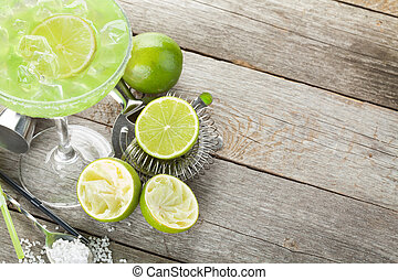 Classic margarita cocktail with salty rim on wooden table with limes and drink utensils