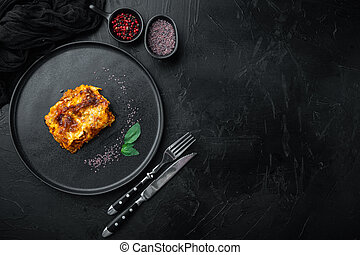Classic meat lasagna with cheese Bechamel and Bolognese sauce, on plate, on black stone background, top view, flat lay, with copy space for text