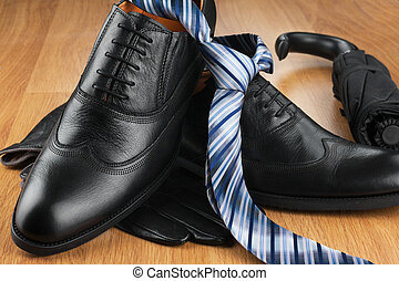 Classic men shoes, tie, gloves, umbrella on wood