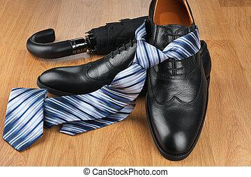 Classic mens black shoes, tie, umbrella, on wooden floor