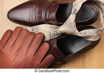 Classic mens brown shoes, tie, gloves, on wooden floor