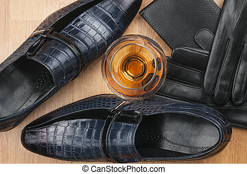 Classic men's shoes and glass of cognac, gloves and purse on wooden desk.