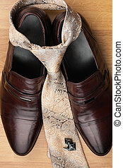 Classic mens shoes, tie, cufflinks on the wooden floor