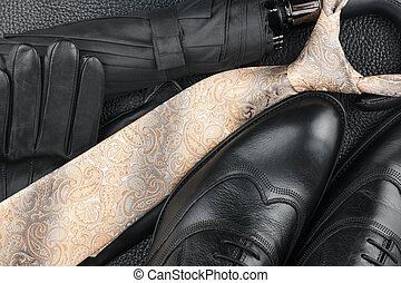 Classic mens shoes, tie, gloves, umbrella on natural skin