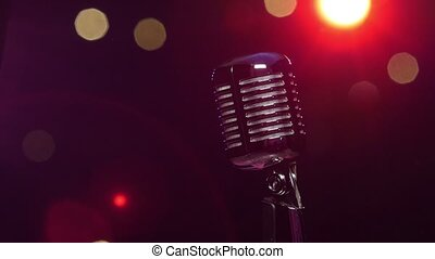 Classic microphone against dark blurry background with bright flashing lights