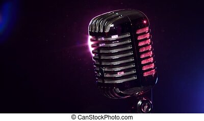 Classic microphone rotating on background lamp stroboscope in dark