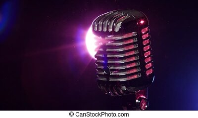 Classic microphone slow rotating on background lamp stroboscope in dark