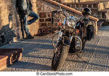 Classic motorcycle and biker at dusk