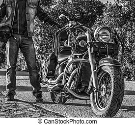 Classic motorcycle and biker on the edge of the road in black and white
