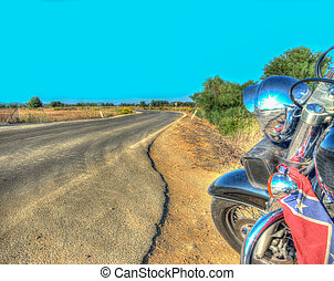 classic motorcycle on the edge of a winding road