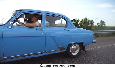 Classic old car traveling on highway on summer day. Young couple driving on country road in vintage automobile. Trip at the retro auto. Concept of summer vacation or holiday. Slow motion Close up