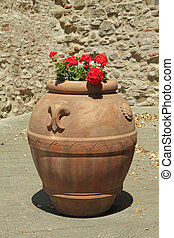 classic planter in tuscan terracotta with red pelargounium flower on street in Italy