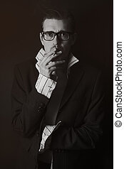 Classic portrait of young man in glasses with cigarette