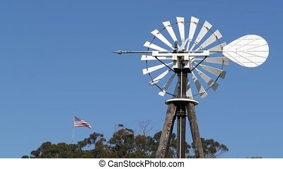 Classic retro windmill, bladed rotor and USA flag against blue sky. Vintage water pump wind turbine, power generator on livestock ranch or agricultural farm. Rural symbol of wild west, rustic suburb.