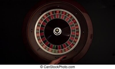 Classic roulette spinning wheel, white ball, on black -...