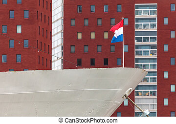 Classic ship with Dutch flag in front of modern buildings