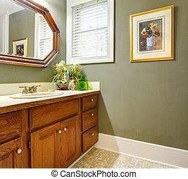 Classic simple green bathroom with wood cabinets.