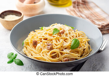 Classic spaghetti pasta carbonara with pancetta, egg yolk and parmesan cheese on concrete background