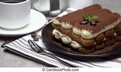 Classic tiramisu dessert on ceramic plate, milk or cream and...