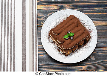 Classic tiramisu dessert on ceramic plate on wooden background