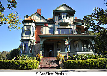 Classic victorian house with hedge in front