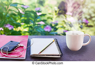 Classic white cup of black coffee with note and pencil on green nature background